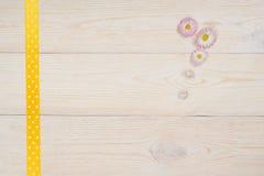Gänseblümchen und Band auf altem weißem Schreibtisch Lizenzfreies Stockfoto