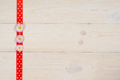 Gänseblümchen und Band auf Retro- Holztisch Stockfotografie