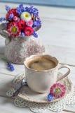 Gänseblümchenblumen und -Tasse Kaffee Lizenzfreie Stockbilder
