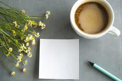 Gänseblümchenblumenstrauß mit coffe und Aufkleber und Bleistifte Stockfotografie