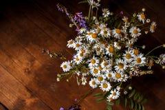 Gänseblümchenblumenstrauß, von Blumen auf dem alten hölzernen Hintergrund lizenzfreie stockbilder
