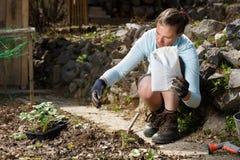 Gärtner, der Huminkörnchen des organischen Düngemittels mit dem Boden, Boden anreichernd mischt lizenzfreie stockbilder