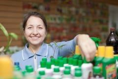 Gärtner wählt Flüssigdünger am Shop Stockbild