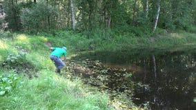 Gärtnermann mit Sensenwerkzeug säubert Teichwasser vom Gras und vom Schlamm 4K stock video