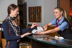 Gäst i hotellet som betalar med kreditkorten på mottagandet Arkivbild