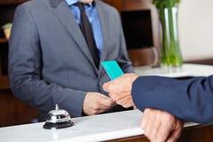 Gäst som ger det nyckel- kortet till hotellreceptionisten Fotografering för Bildbyråer