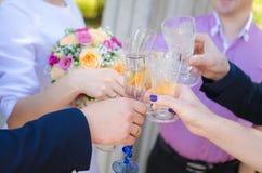 Gäste an einer Hochzeit mit der Braut und dem Bräutigam klirren Gläser Champagner Lizenzfreie Stockfotos