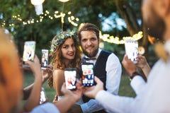 Gäste mit den Smartphones, die draußen Foto der Braut und des Bräutigams am Hochzeitsempfang machen Lizenzfreie Stockfotografie
