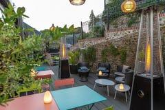 Gästehaus, Gartenrestaurant, Farbmetalltabellen und Aufenthaltsraum im Freien mit Blumendekorationen, gaz Heizsystem, lizenzfreies stockbild