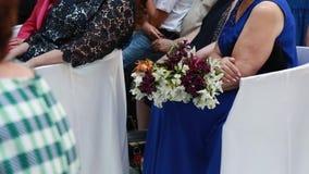 Gäster med blom- buketter som sitter på en gifta sig ceremoni lager videofilmer