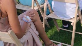 Gäster med buketter för en blomma som sitter på en gifta sig ceremoni arkivfilmer