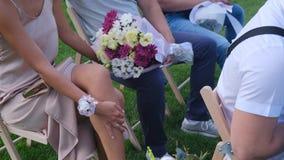 Gäster med buketter för en blomma som sitter på en gifta sig ceremoni stock video