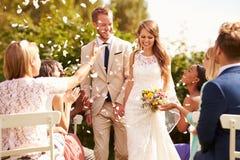 Gäster som kastar konfettier över bruden och brudgummen At Wedding Royaltyfri Fotografi