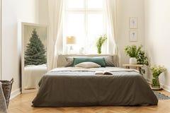 Gästhemsovruminre med en säng, grupper av lösa blommor och en vintergrön trädreflexion i spegeln Verkligt foto arkivbild