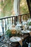 Gästkort på en platta med bröllopgarneringar i en lantlig stil i en gazebo nära vattnet Royaltyfri Fotografi