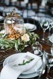 Gästkort på en platta med bröllopgarneringar i lantlig stil på en trätabell Royaltyfria Bilder