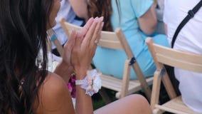 Gästkvinna Applaused som sitter på en gifta sig ceremoni lager videofilmer