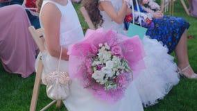 GästLittla flickor med buketter för en blomma som sitter på en gifta sig ceremoni stock video