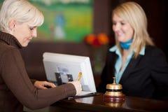 Gästpåfyllning en formular på hotellräknaren royaltyfri foto