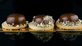 Gładki zoom od za trzy francuskich minych mousse ciasta deserach zakrywających z czekoladowym glazerunkiem zdjęcie wideo