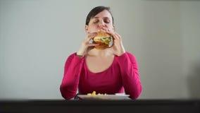 Głodna młoda kobieta greedily je kanapkę zdjęcie wideo