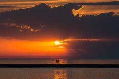 Gå över vatten på solnedgången Arkivfoto