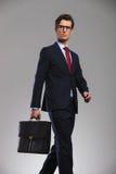 Gå affärsmannen som rymmer en bort resväska och blickar Royaltyfri Foto