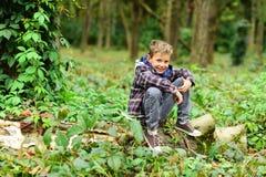 Gå att campa med mig Den lilla ungen tycker om campa tur Den lilla pojken sitter på träd Den förtjusande ungen kopplar av i trän  royaltyfri fotografi