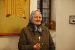 Gå att kyrktaga Farmor med en stearinljus i kyrkan Fotografering för Bildbyråer