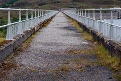 Gå banan överst av den hydroelektriska fördämningväggen i Skottland Arkivbild