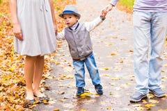 gå barn för familjpark Föräldrar som rymmer händer av lite, behandla som ett barn på sonen från höstlig färgrik skog för båda sid Arkivfoton