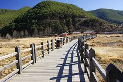 Gå den wood forntida bron för förbindelsebro, över Lugu sjön i blå himmel royaltyfri bild