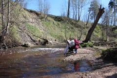 Gå dottern med hans fader i natur nära floden royaltyfri bild