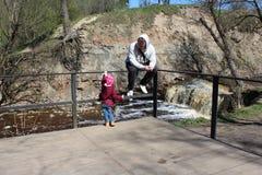 Gå dottern med hans fader i natur nära floden royaltyfria foton