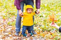 gå för faderson Baby som tar första steg med faderhjälp i höstträdgård i staden Royaltyfri Foto