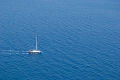 Gå för segelbåt som motoriseras i mitt av blåtten och tranqen royaltyfri bild