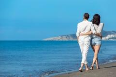 gå för strandpar Unga lyckliga interracial kopplar ihop att gå på det le innehav för stranden runt om varje annat Arkivbild