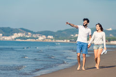 gå för strandpar Unga lyckliga interracial kopplar ihop att gå på det le innehav för stranden runt om varje annat Royaltyfria Bilder
