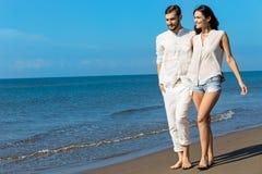 gå för strandpar Unga lyckliga interracial kopplar ihop att gå på det le innehav för stranden runt om varje annat Royaltyfria Foton