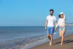 gå för strandpar Unga lyckliga interracial kopplar ihop att gå på det le innehav för stranden runt om varje annat Royaltyfri Bild