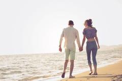 gå för strandpar Unga lyckliga interracial kopplar ihop att gå på det le innehav för stranden runt om varje annat Fotografering för Bildbyråer