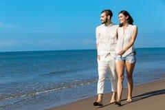 gå för strandpar Unga lyckliga interracial kopplar ihop att gå på det le innehav för stranden runt om varje annat Royaltyfri Fotografi