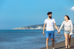 gå för strandpar Unga lyckliga interracial kopplar ihop att gå på det le innehav för stranden runt om varje annat Arkivfoton