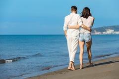 gå för strandpar Unga lyckliga interracial kopplar ihop att gå på det le innehav för stranden runt om varje annat Royaltyfri Foto