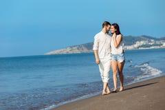 gå för strandpar Unga lyckliga interracial kopplar ihop att gå på det le innehav för stranden runt om varje annat Arkivbilder