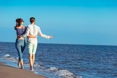 gå för strandpar Unga lyckliga mellan skilda raser par som går på stranden Arkivfoto