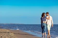 gå för strandpar Unga lyckliga mellan skilda raser par som går på stranden Fotografering för Bildbyråer