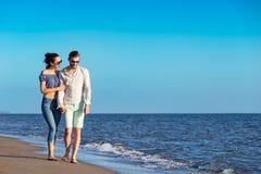 gå för strandpar Unga lyckliga mellan skilda raser par som går på stranden Arkivfoton