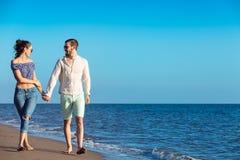 gå för strandpar Unga lyckliga mellan skilda raser par som går på stranden Royaltyfri Bild