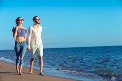 gå för strandpar Unga lyckliga mellan skilda raser par som går på stranden Royaltyfria Bilder